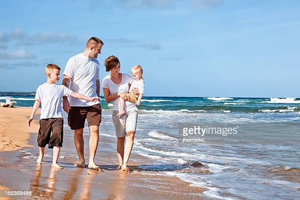 Quatre membres d'une famille marchant sur la plage