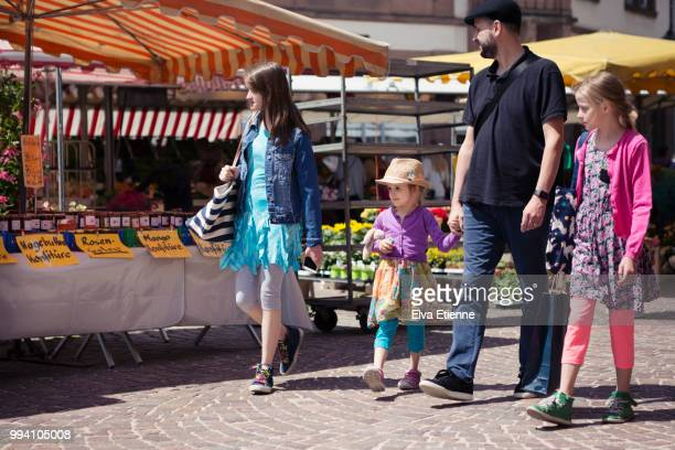 family of four, walking through a market place in an old german town - man met een groep vrouwen stockfoto's en -beelden
