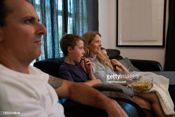 """family of four watching tv in living room. - """"martine doucet"""" or martinedoucet stock pictures, royalty-free photos & images"""