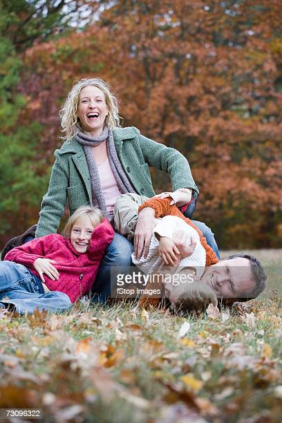 Family of four wrestling in park