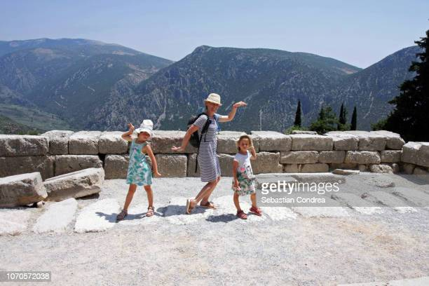 family of girls dancing a traditional dance in the warmth of the sun on the pedestal, oracle of delphi,travel,greece - girls of the sun stock pictures, royalty-free photos & images