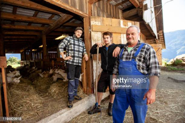family of goat farmers in front of stable - stock photo - dairy stock pictures, royalty-free photos & images