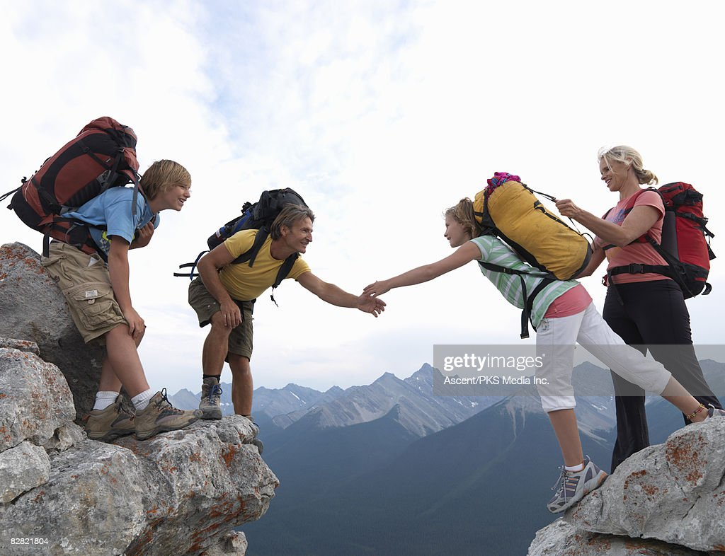 Helping Each Other: Family Of Hikers Helping Each Other Over Rock Gap Stock
