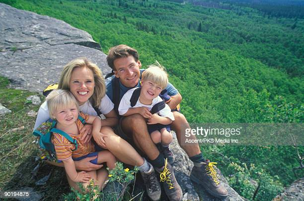Family of hikers look at camera, forest below
