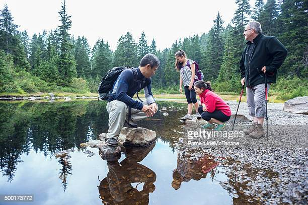 Family of Hikers Resting at Shoreline of Alpine Lake, Canada