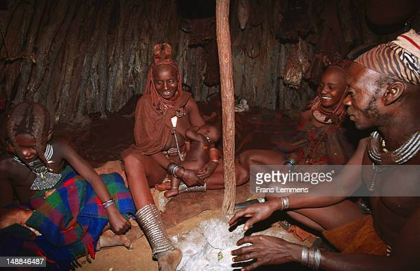 Family of Himba tribe around fire inside hut.