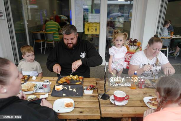 Family of holiday-makers from Swansea enjoy a cooked breakfast at a restaurant with outside tables on August 19, 2021 in Newquay, Cornwall, England....