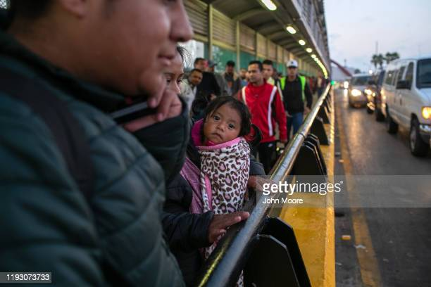 A family of Honduran asylum seekers stands on the international bridge from Mexico to the United States on December 09 2019 in the border town of...