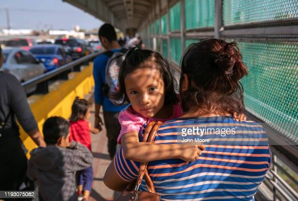 A family of Mexican asylum seekers walks to the center of the international bridge between Mexico and the United States to officially request...
