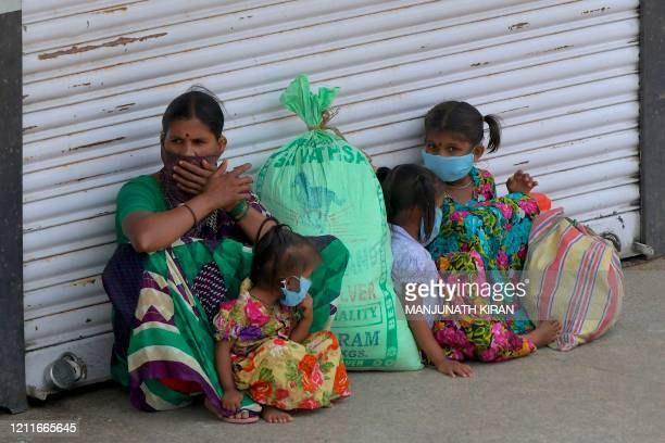 Family of migrant workers wait to board a bus back to their hometowna as Karnataka government opened inter-state transport buses for people stranded...