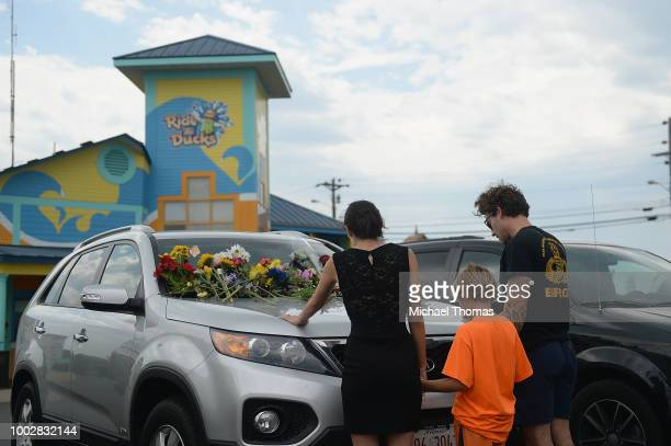 A family of mourners pause for a moment of prayer at Ride The Ducks Tours on July 20 2018 in Branson Missouri Hundreds of mourners stopped by the...