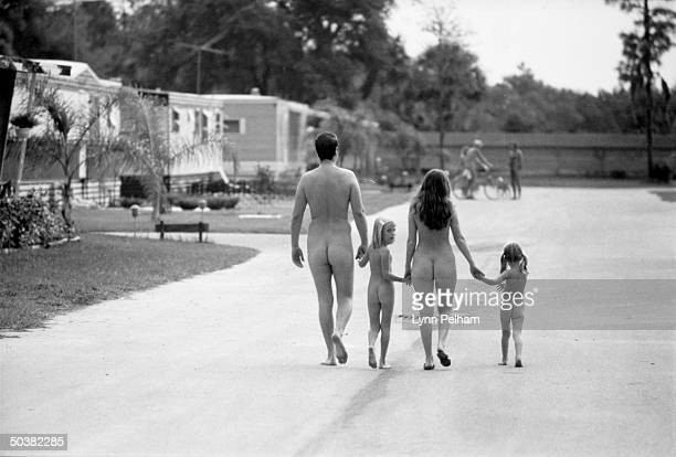 Family of nudists strolling down the street