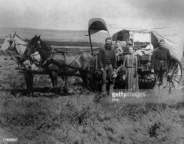A family of pioneer settlers pose next to their covered wagon 1886