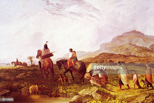 A family of Plains Indians transport their possessions on a travois a triangular frame of wooden poles covered with buffalo rawhide which could be...