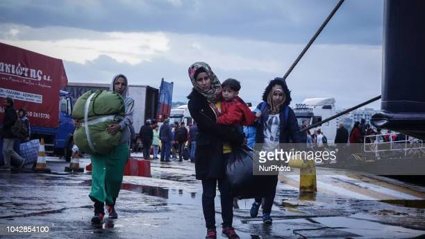 A family of refugees carry its belongings items after they disembark from a ferry at the Port of Piraeus 29 September 2018 Thousand migrants and...