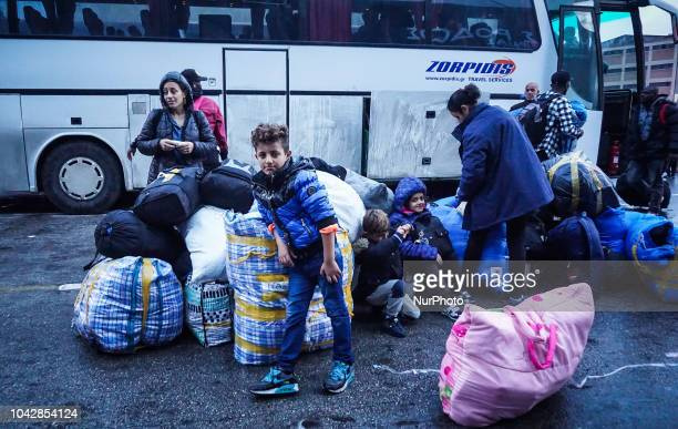 A family of refugees wait to board a bus following they disembark from a ferry at the Port of Piraeus 29 September 2018 Thousand migrants and...