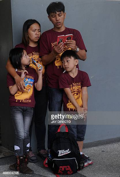 A family of Roman Catholic devotees pray as they attend a Celebration of the Way of the Cross service at a Church in suburban Manila on April 2 2015...