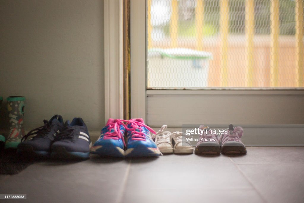 Family of shoes of different sizes sitting near home door : Stock Photo