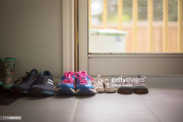 family of shoes of different sizes sitting near home door - schoen stockfoto's en -beelden
