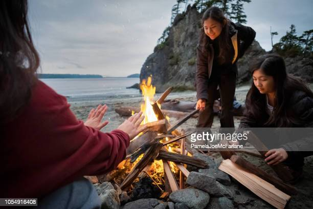 family of sisters building campfire on remote winter beach, canada - hygge stock pictures, royalty-free photos & images
