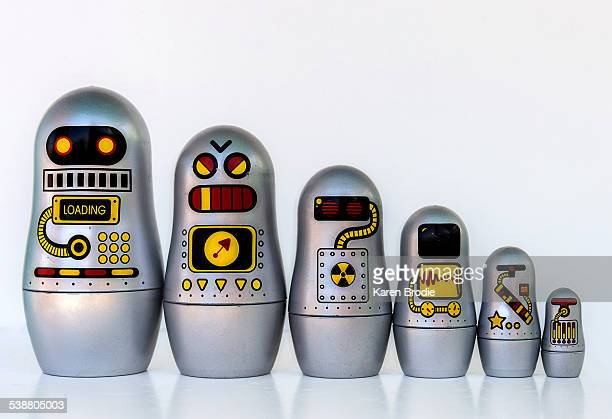 Family of six nesting robot toys lined up biggest to smallest on a white background