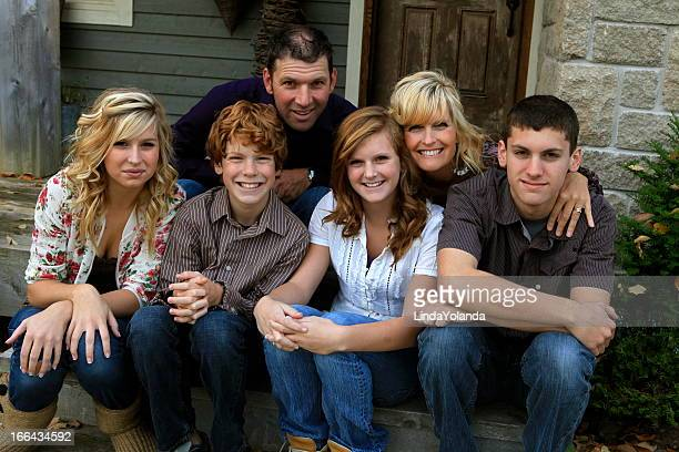 Family of six sitting in front step of their house