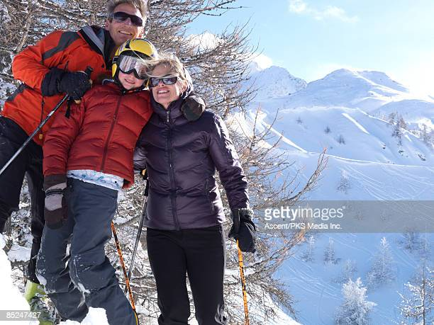 family of skiers/boarders on mountain slope - バルドネキア ストックフォトと画像