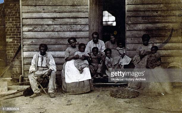 Family of slaves at the Gaines' house. African American slave family posed in front of a wooden house, Washington, D.C. Or Hampton, Virginia.