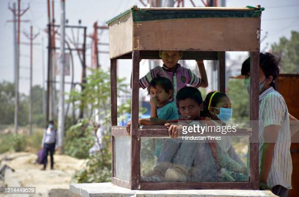 Family of stranded migrant workers seen at an empty food stall, at NH24 road on May 21, 2020 in Ghaziabad, India.