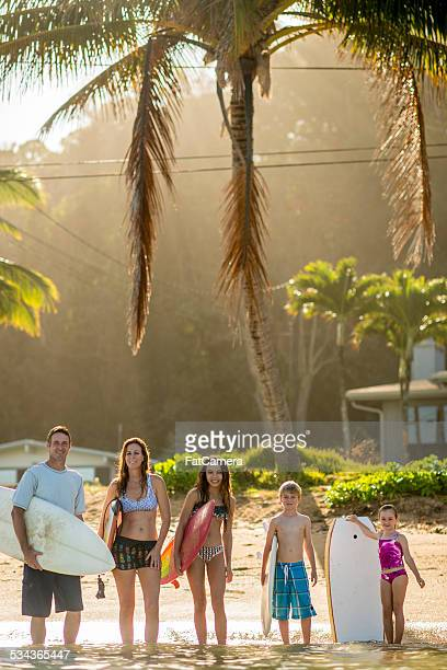 Family of surfers in tropical climate