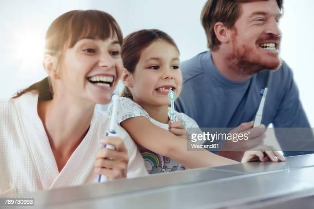 family of three brushing their teeth in front of big mirror - zahnpflege stock-fotos und bilder