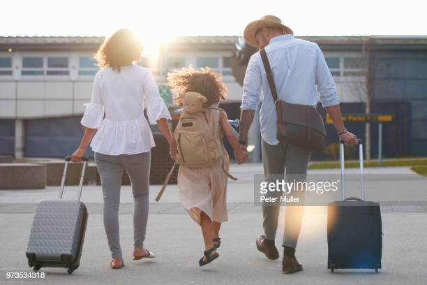 family of three going on vacation - skipping along stock-fotos und bilder