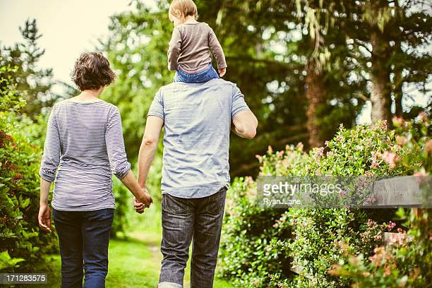 Family of three hiking together in garden
