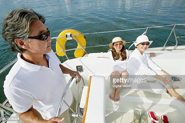 Family of Three in a Sailing Boat, Father at the Ship's Wheel