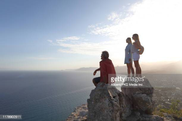 family of three look off from rock summit - s'évader du réel photos et images de collection