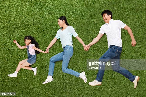 a family of three lying on the grass do running posture - 横向きに寝る ストックフォトと画像