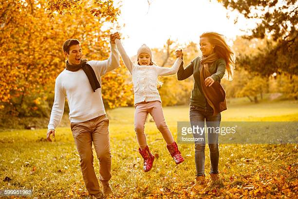 Family of three playing in autumn park