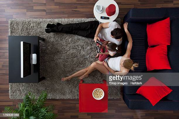 A family of three playing video games in their living room, overhead view