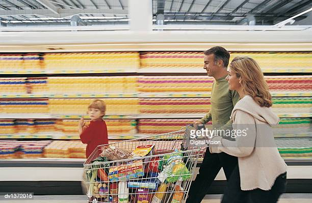 family of three pushing a shopping trolley quickly down a supermarket aisle - caddie rempli photos et images de collection