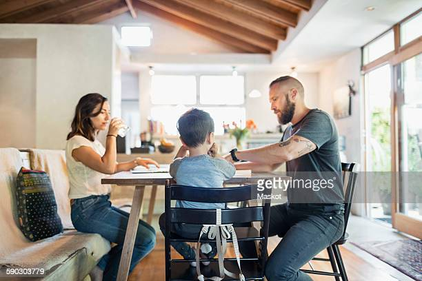 Family of three sitting at dining table in house