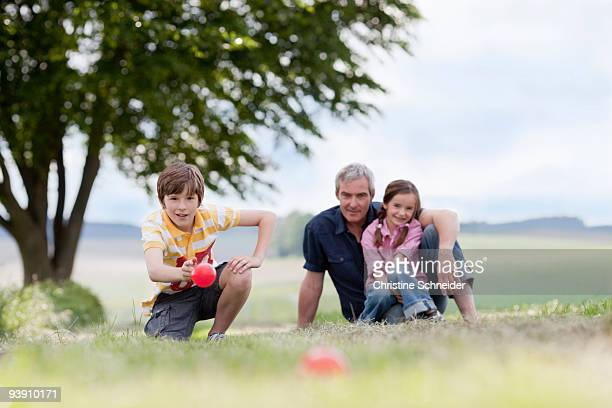 family of three sitting on the grass