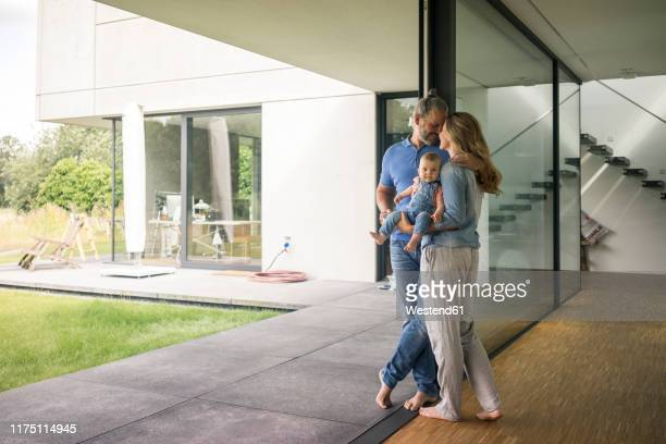 family of three standing at the window at home - wealth stock pictures, royalty-free photos & images