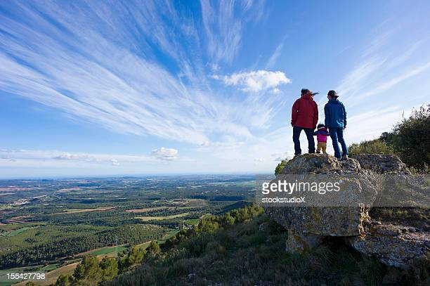 Family of three standing on a hill looking at a landscape