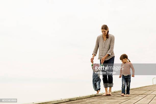 Family of three walking on pier against clear sky