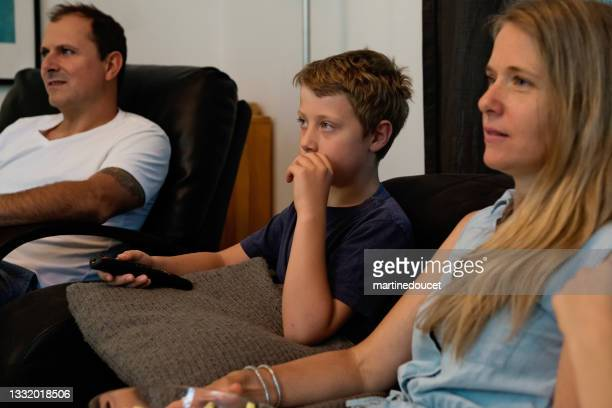 """family of three watching tv in living room. - """"martine doucet"""" or martinedoucet stock pictures, royalty-free photos & images"""