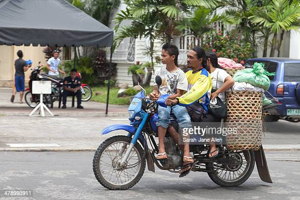 CONTENT] Family of three with bags and baskets all loaded onto one motorcycle and riding down the road