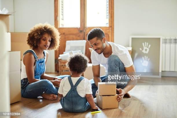 familie van drie met karton vakken in het nieuwe huis - afro amerikaanse etniciteit stockfoto's en -beelden