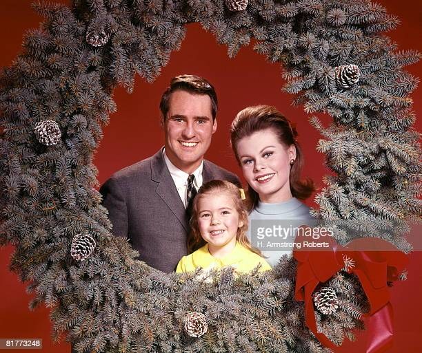 Family Of Three With Little Daughter Framed By Christmas Wreath Portrait Man Woman Girl.