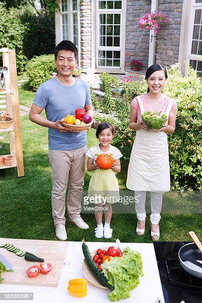 A family of three with vegetables in the outdoor kitchen