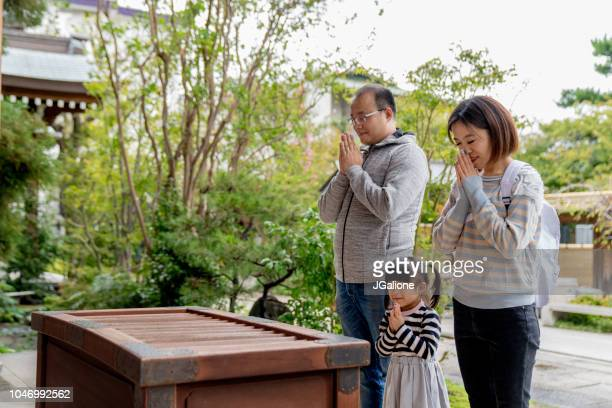 family of tourists praying at a japanese temple - shrine stock pictures, royalty-free photos & images